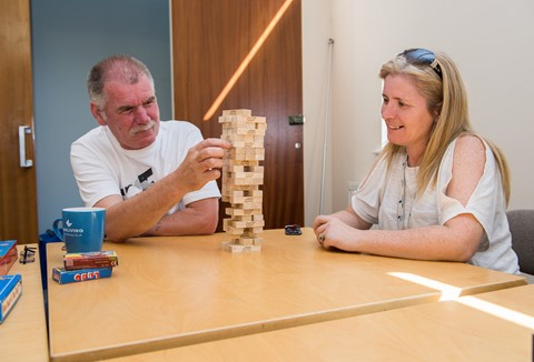 Support worker and client playing Jenga