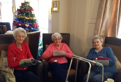 Care home residents with twiddle muffs